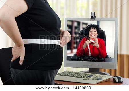Fat woman in black clothes measures her waist in front of monitor. She intends to reduce her stomach size with the help of virtual doctor. Cheerful physician in monitor explains how to do it