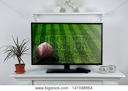Watching football game on tv at home.
