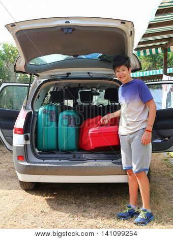 Boy Loads A Little Red Suitcase In The Trunk