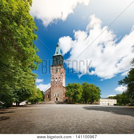 Turku Cathedral on sunny day with blue cloudy sky in background and empty square in foreground