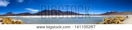 Lake panorama with snow-capped mountains on a sunny day
