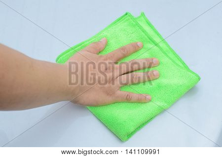 A man cleaning car with green microfiber cloth
