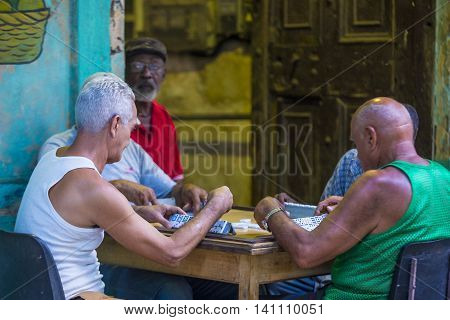 HAVANA CUBA - JULY 18 : Unidentified men play dominos on the street on July 18 2016 in Havana Cuba. Domino is one of the most popular games in Cuba