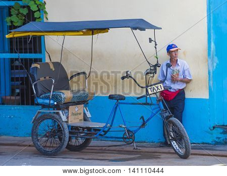 HAVANA CUBA - JULY 18 : A Cuban rickshaw driver in old Havana street on July 18 2016. Rickshaw are a popular way of transport in Cuba