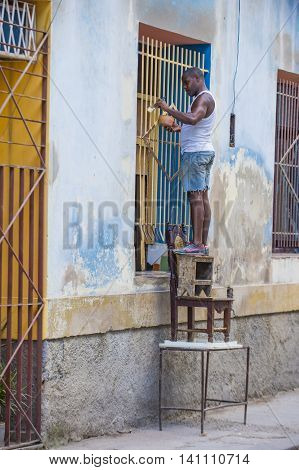 HAVANA CUBA - JULY 18 : A Cuban man painting bars in old Havana street on July 18 2016. The historic center of Havana is UNESCO World Heritage Site since 1982.
