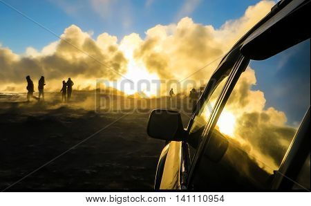 People walking through smoke in the sunset from the window of a car