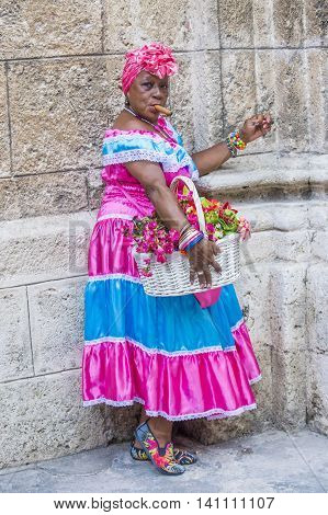HAVANA CUBA - JULY 18 : A portrait of a Cuban woman smoking cigar in old Havana street on July 18 2016. Cuba now exports more than 90 million cigars a year