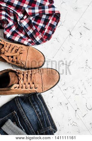 Jeans checkered shirt and suede boots a light background. Women's clothing. Retro style top view