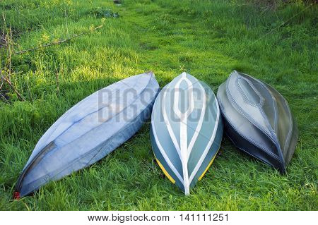 Three overturned boats lie on the green grass