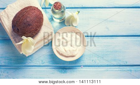 Organic spa products. Coconut coconut oil and cream on wooden background. Selective focus is on coconut. Place for text. Toned image.