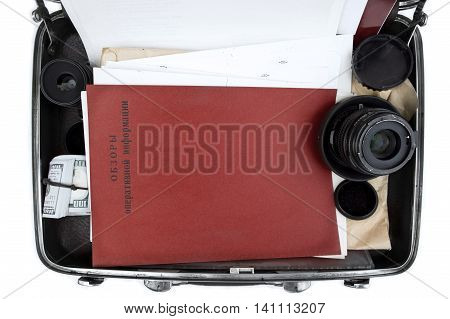 An open briefcase with retro red folder and text Operative Information Review in russian concept of top secrets overhead filtered shot