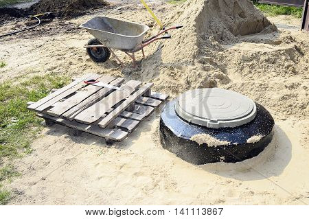 Construction site with new armed manholes cart sand and equipment.