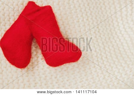 Pair Christmas red miniature felt boots for decoration on a white knitted cap. With place for your text, for background use.