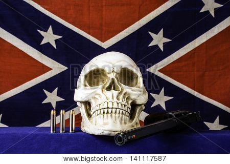 human skull with three bullets and 357 magnum revolver with house fly on barrel and confederate flag background