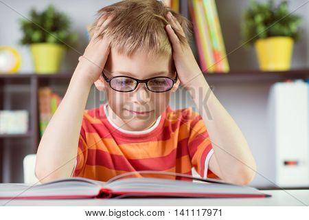 Elementary School Boy At Desk Reading Boock