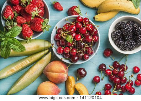 Healthy summer fruit variety. Sweet cherries, strawberries, blackberries, peaches, bananas, melon slices, peaches and mint leaves on blue wooden backdrop, top view