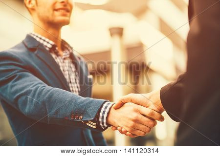 Two businessman shaking hands during the meeting outdoor. Selective focus on hands.