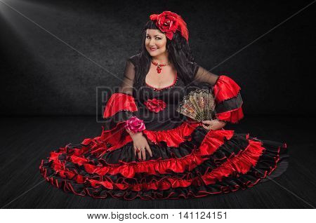 Mature female flamenco dancer sits on a stage floor. The woman wears red and black flamenco floor-length gown with frills. She holds a fan with left hand and looks at camera