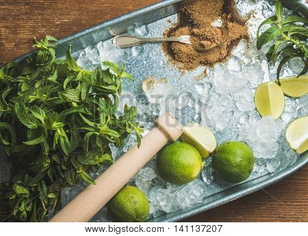 Ingredients for making mojito summer cocktail in metal tray over rustic wooden background, top view, horizontal composition