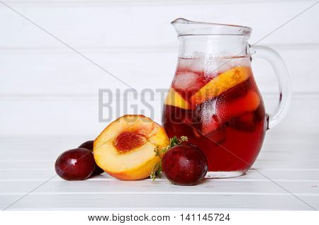 Iced fruit compote with peaches and plums. Cold summer drink with fruit in a basket in the back.