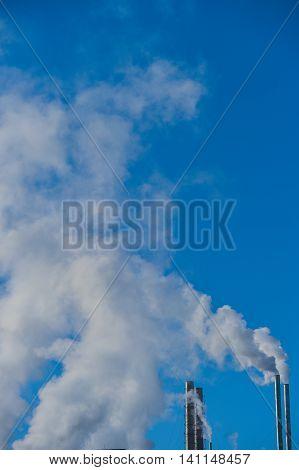 Smoke Stack Emitting Against Blue Sky Industry
