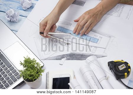Architect working on blueprint. Architects workplace - architectural project, blueprints, ruler, calculator, laptop and divider compass. Construction concept. Engineering tools. Top view