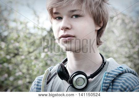 Portrait of teenager with headphones, toned in retro style, shallow depth of field