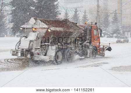 Special technique removes the snow from the street during a snow storm in poor visibility. Snow storm in the city of Cheboksary Chuvash Republic Russia. 01/17/2016