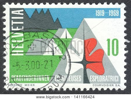 MOSCOW RUSSIA - CIRCA APRIL 2016: a post stamp printed in SWITZERLAND shows Swiss Girl scouts' emblem and a camp dedicated to the 50th anniversary of Swiss Girl Scouts circa 1969