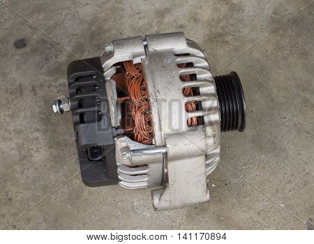 Cracked and old used alternator for the car on concrete floor
