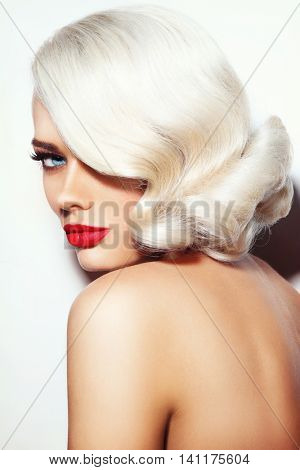 Portrait of young beautiful platinum blonde tanned woman with vintage hairdo and red lipstick