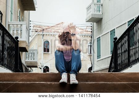 sad woman wearing a hat and hugging knees on stair she is lonely most of the time dark tone