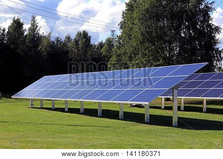 Solar panels placed on green grass field in city as seen in early evening sunlight.