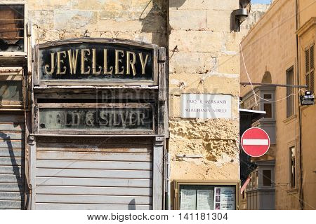 old traditional shop and road signs Merchants Street Valletta Malta. June 2016