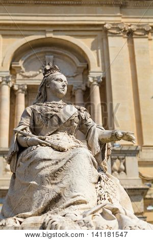 Statue of Queen Victoria Republic Square Valletta Malta Europe. With the limestone National Library of Malta in background