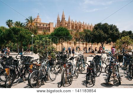 Palma de Mallorca Spain - May 27 2016: A lot of bicycles stand in the parking lot in front of the La Seu Cathedral of Palma de Mallorca and La Almudaina Royal Palace Spain.