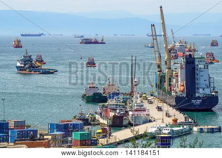 Labuan,Malaysia-Aug 4,2016:Container cargo freight ship with working crane loading bridge in shipyard at Labuan port.The port loads more then 99 percent of containerized goods through Labuan island.