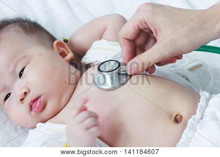 Professional pediatrician examining infant. Doctor using a stethoscope to listen to kid's chest checking heartbeat. Two months baby asian girl lying on sickbed in hospital.