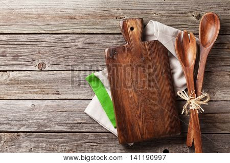 Cutting board and utensils over towel on wooden kitchen table. Top view
