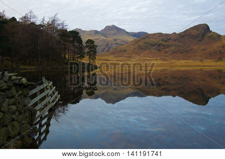 Blea Tarn with reflections of fnece and the Langdales Cumbria
