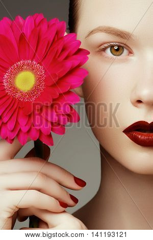 Beauty Fashion Model Woman Face. Portrait With Red Flower. Red L