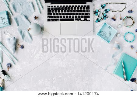 Flat lay top view office table desk. Mint workspace with laptop diary mint decor accessories and spool on grey concrete background.