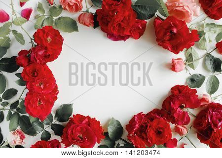 flat lay frame with red roses branches leaves and petals isolated on white background. top view