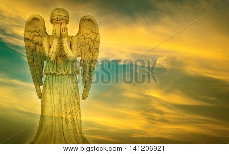 Weeping beautiful angel over bright sky background