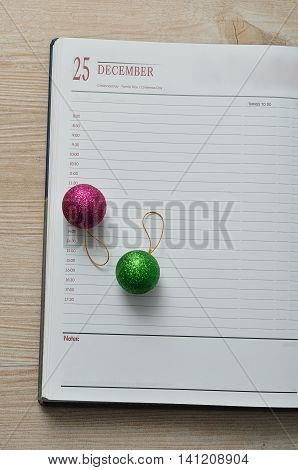 Diary open on the 25th of December decorated with baubles