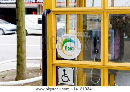 LUXEMBOURG LUXEMBOURG - Post Luxembourg sticker on yellow phone boothe in the center of Luxembourg. Former Entreprise des Postes et Télécommunications branded as POST Luxembourg and abbreviated to POST is a mail and telecommunications semi government-owne