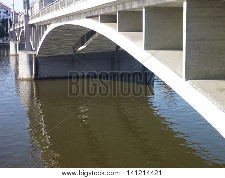 Concrete Bridge Arch Reflected In River Water