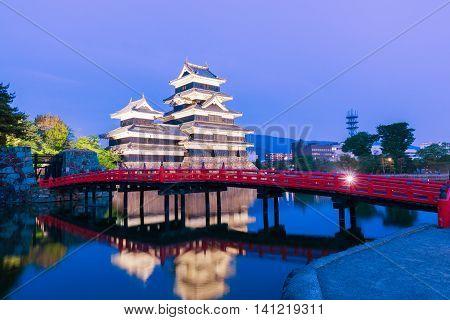 Matsumoto Castle (matsumoto-jo) Historic Landmark At Night With Beautiful Reflection In Water.