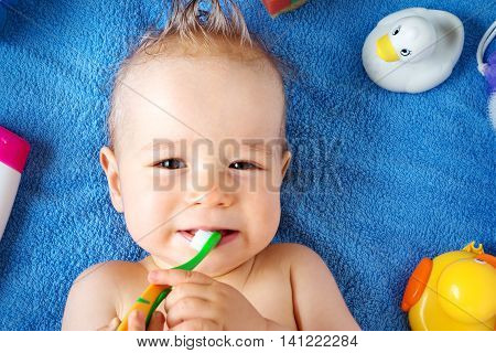 one year old baby lying on towel with washing tools