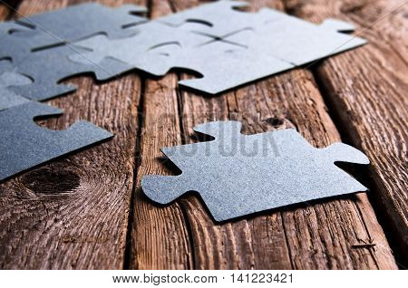 Incomplete puzzles lying on wooden rustic boards. Conceptual of innovation, solution finding and integration.